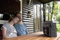 Man and woman listening to radio in cottage at allotment garden — Stock Photo