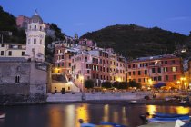 Italy, Vernazza, View of church with harbour at dusk — Stock Photo