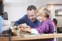 Père et fils, réparation de planche à roulettes — Photo de stock