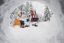 Молодые женщины, сидя у костра место в зимнем лесу, Зальцбург, Австрия — стоковое фото
