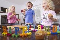 Children celebrating birthday in kitchen with cakes — Stock Photo