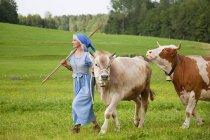 Mujer madura con la vaca en la granja - foto de stock