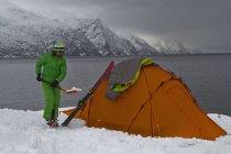 Норвегия, удаление снега с лопатой вблизи палатка лыжник — стоковое фото