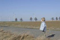 Garçon debout sur la route, éolienne en arrière-plan — Photo de stock