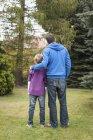 Батько і син, стоячи в саду — стокове фото