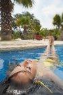 Молодая женщина расслабляется в бассейне — стоковое фото