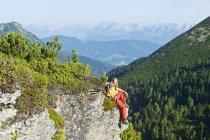 Escursionista seduto sulla roccia — Foto stock