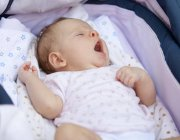 Niedliche Baby-Mädchen in Krippe gähnen — Stockfoto