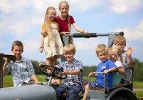 Grupo de niños sentados en tractor viejo - foto de stock