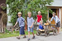 Group of children playing with hand cart in front of farmhouse — Stock Photo