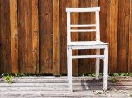 Cadeira branca contra a parede de madeira marrom — Fotografia de Stock