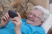 Mujer mayor usando teléfono inteligente, sonriendo - foto de stock