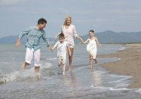 Spain, happy family running on beach together — Stock Photo