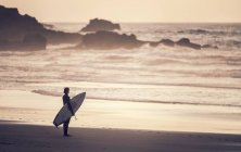 Португалия, Алгарве, Сагреш, живописный закат пейзаж с серфер силуэт с доски для серфинга в Прае делать Кастележу, глядя на океан — стоковое фото