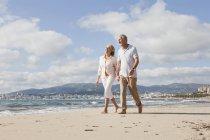 Старший пара, прогулянки по пляжу, посміхаючись — стокове фото