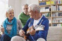 Senior man playing electric guitar, man and woman sitting besides — Stock Photo