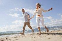 Старший пара вздовж пляжу, посміхаючись — стокове фото