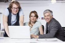 Hommes et femme avec ordinateur portable au bureau, portrait — Photo de stock