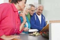 Seniores homens e mulheres cozinhar alimentos — Fotografia de Stock