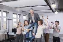 Colleagues carrying mature man on shoulder, smiling — Stock Photo