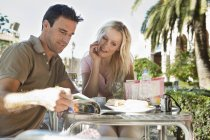 Spain, Mallorca, Palma, Couple sitting at table in cafe, smiling — стоковое фото