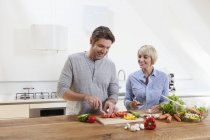 Mature couple chopping vegetables in kitchen, smiling — Stock Photo