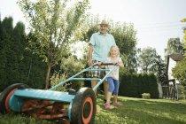 Grand-père avec des enfants tondre la pelouse — Photo de stock