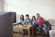 Homens e mulheres assistindo TV em casa — Fotografia de Stock