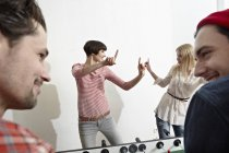 Men and women playing table soccer — Stock Photo