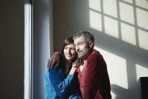 Couple assis à la fenêtre, souriant à la maison — Photo de stock