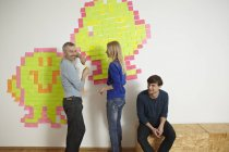 Men and woman with paper note on wall — Stock Photo