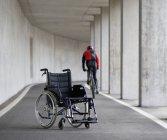 Junger Mann auf Mountainbike mit Rollstuhl im Vordergrund — Stockfoto