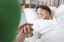 Mitte erwachsene Frau hält Hand der Seniorin — Stockfoto