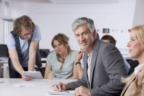 Mature man smiling while colleagues working in background — Stock Photo