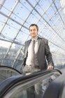 Uomo d'affari sulla scala mobile, ritratto — Foto stock