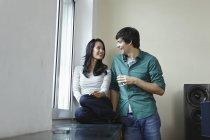 Молодая пара у окна, улыбающаяся дома — стоковое фото