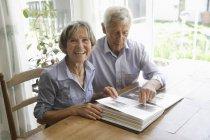 Старший пара з фотоальбому, посміхаючись — стокове фото