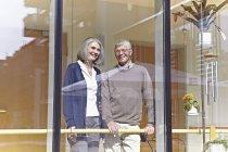 Senior couple looking through window, smiling — Stock Photo