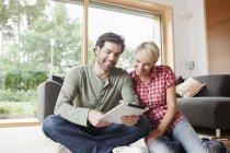 Älteres Paar mit digital-Tablette im Wohnzimmer — Stockfoto