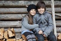 Девочка и мальчик сидят на стоге дров, улыбаются, рисуют портрет — стоковое фото