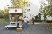 Family loading boxes into truck for moving house — Stock Photo