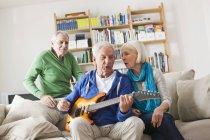 Senior spielt E-Gitarre, Mann und Frau sitzen nebeneinander — Stockfoto