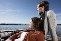 Pareja sentados en el embarcadero en el lago - foto de stock