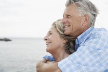 Senior couple embracing at harbour, smiling — Stock Photo