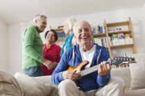 Älterer Mann spielt E-Gitarre, Mann und Frau im Hintergrund — Stockfoto