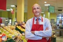 Зрелый мужчина, стоящий в супермаркете, улыбающийся, портрет — стоковое фото