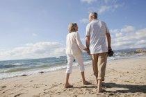 Старший пара прогулянка по пляжу — стокове фото
