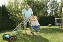 Grandfather with children mowing lawn — Stock Photo
