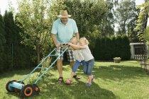 Дід з дітьми покіс газонів — стокове фото