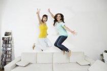Молоді жінки, весело і стрибати на дивані — стокове фото